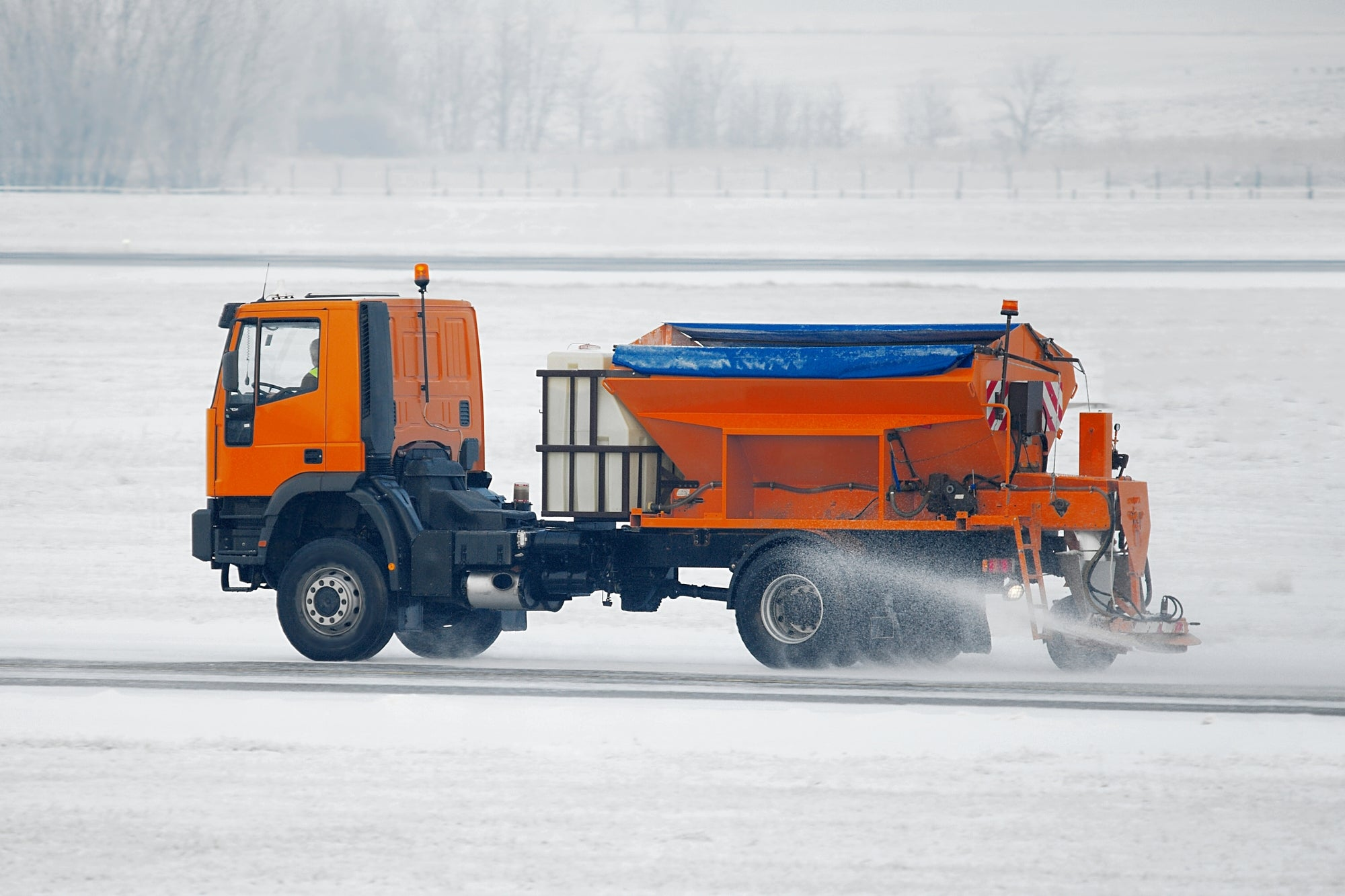 An orange truck spreading salt on a snowy airport runway