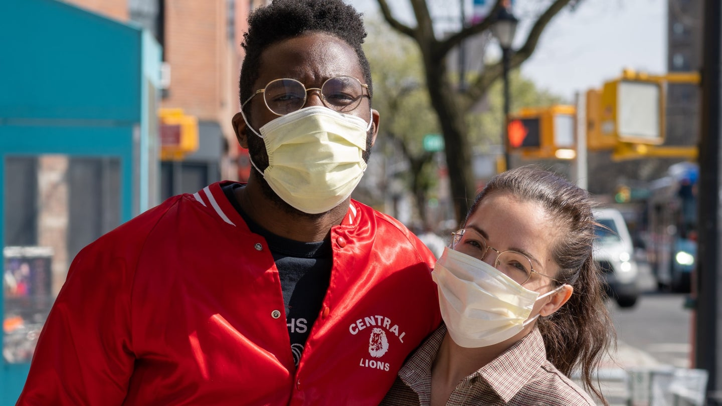 Two people wearing cloth face masks with their arms around each other on a New York City sidewalk on a sunny day.