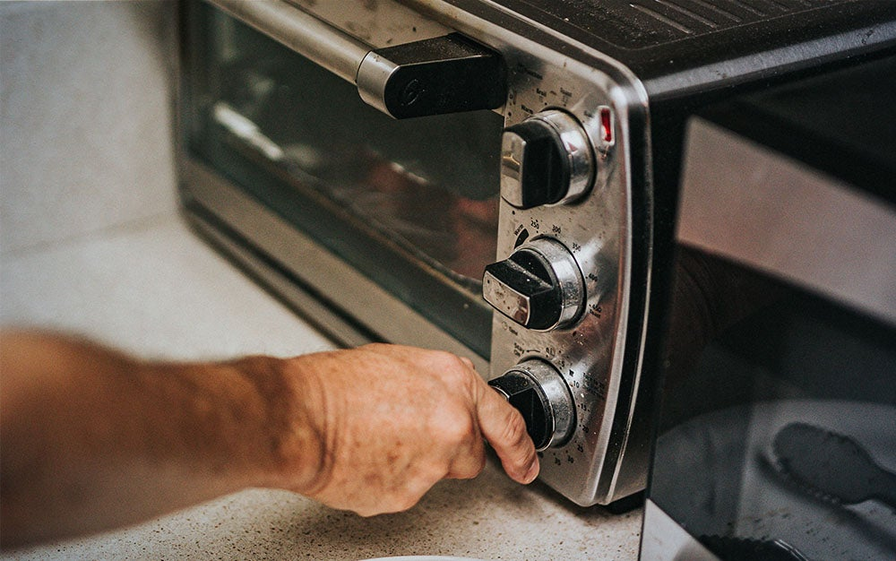 person turning the dial on the best toaster oven