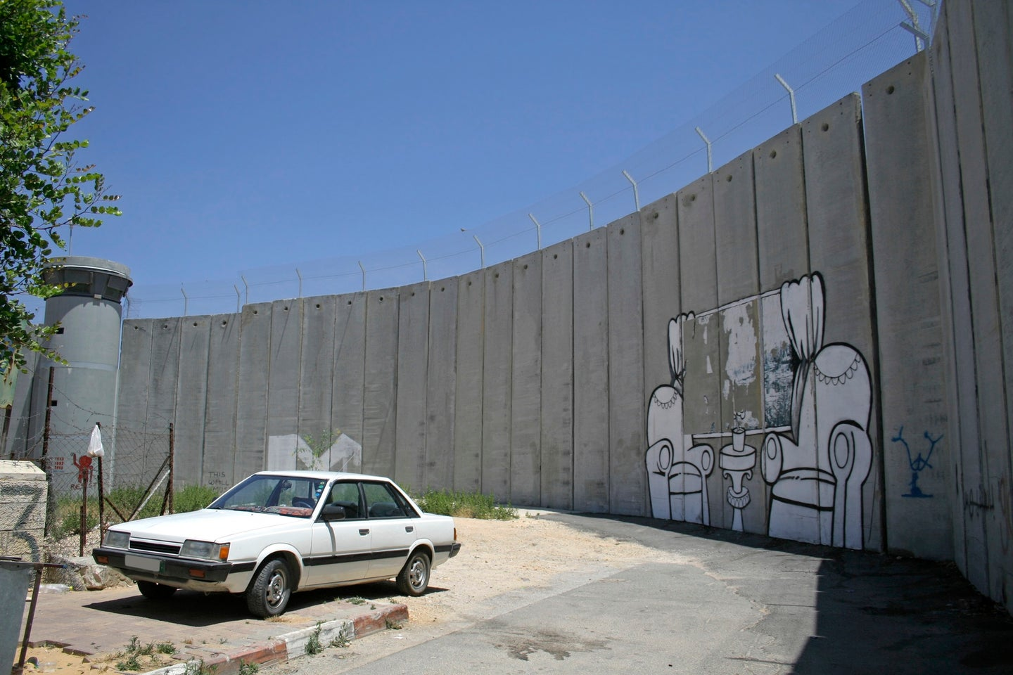 The graffiti-marked West Bank wall with a white car in front
