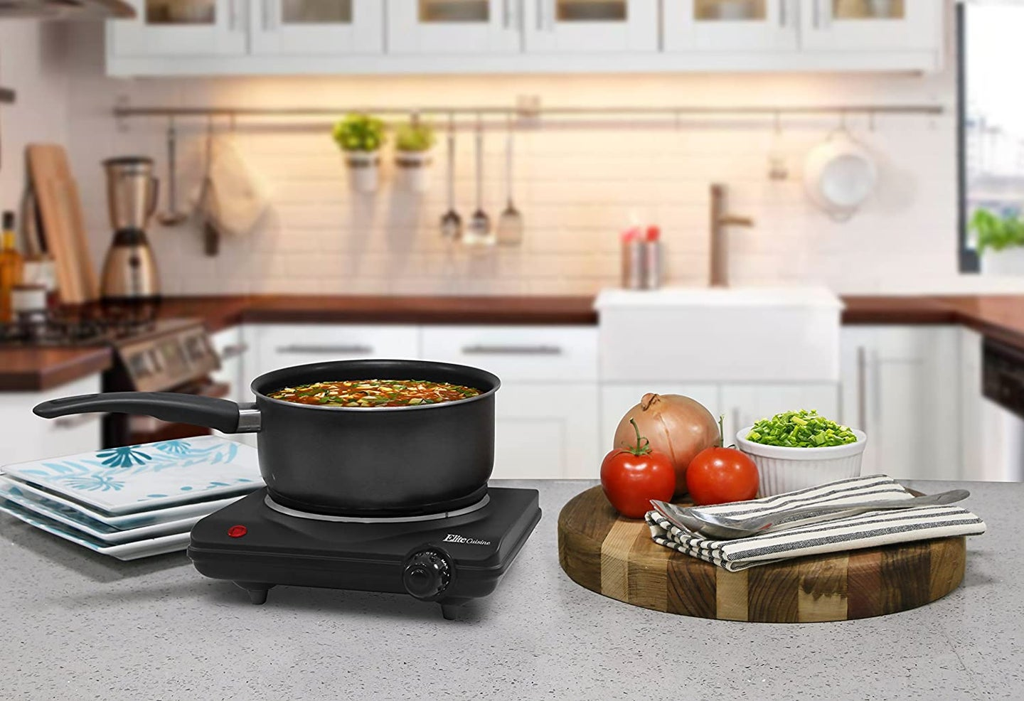 induction cooktop on a kitchen counter with plates and vegetables
