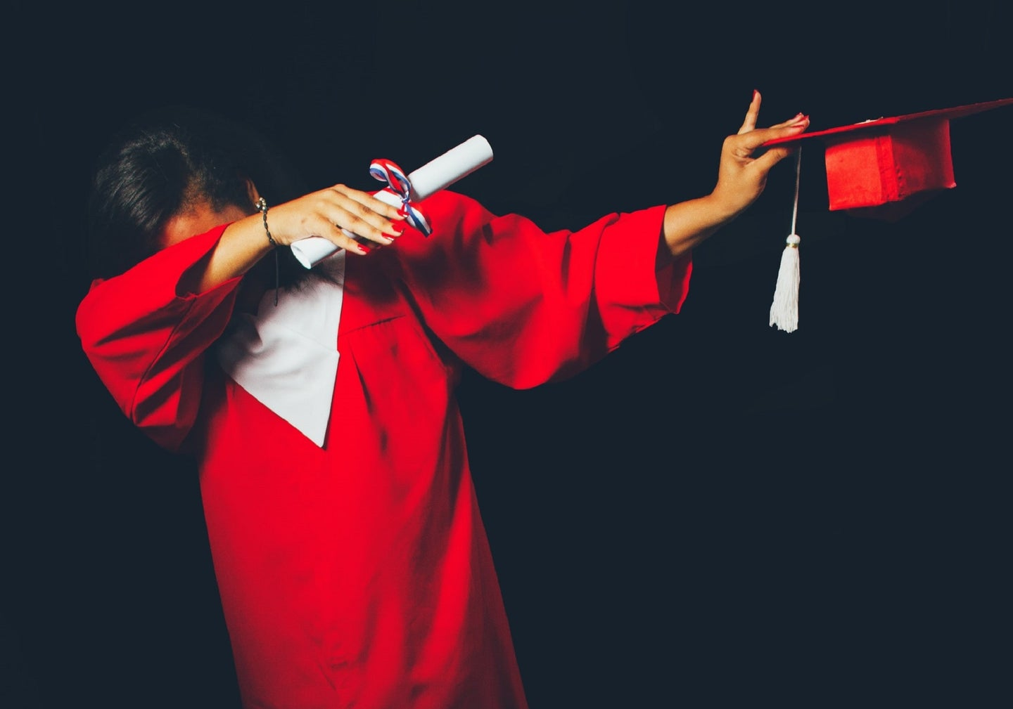 A student in a red graduation gown dabbing