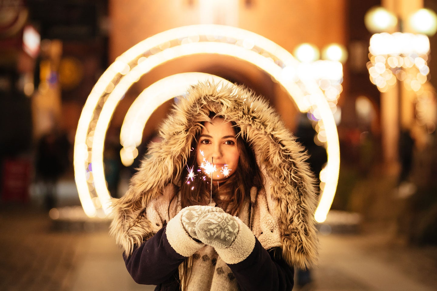woman in a winter coat wearing the best mittens and holding sparklers