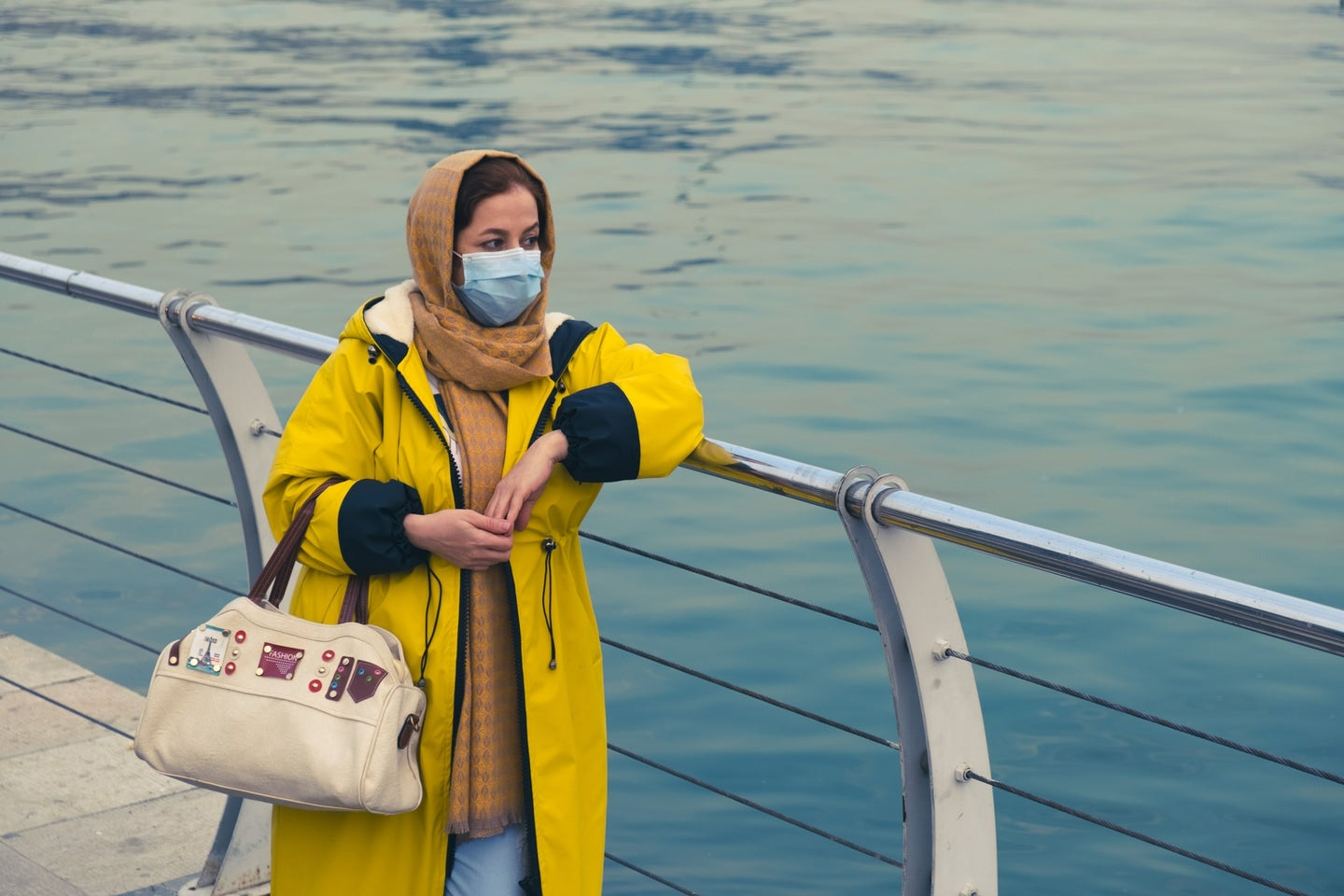 A woman in mask, head scarf and yellow rain jacket stands along the water