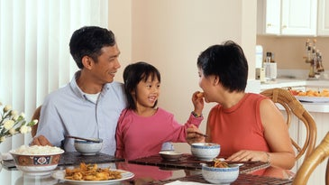 Chinese parents and kid have a meal in their dining room