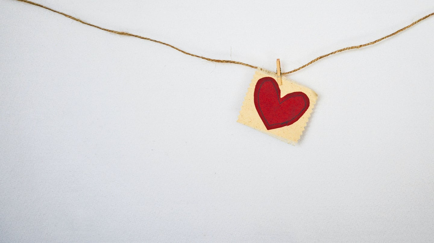 heart on a piece of paper that is hanging on a string