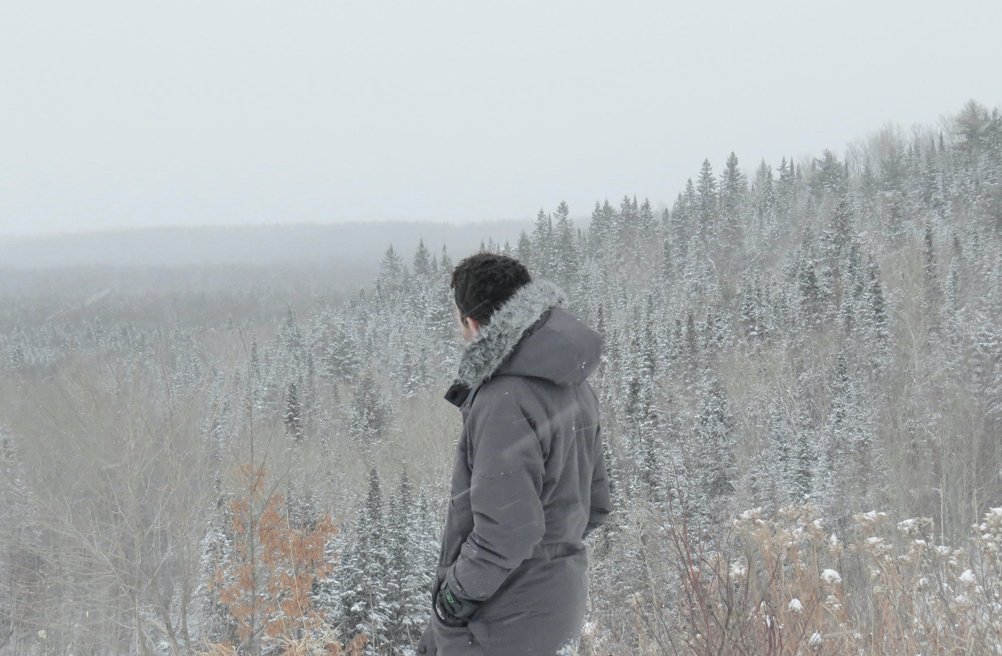 guy in a heated vest and jacket standing on a snowy mountain with trees in the background