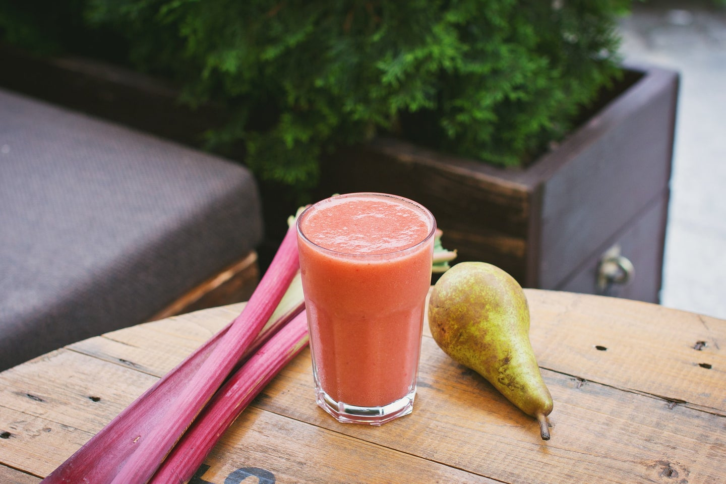 fruits and vegetables on a table next to a glass of colorful liquid for a juice cleanse