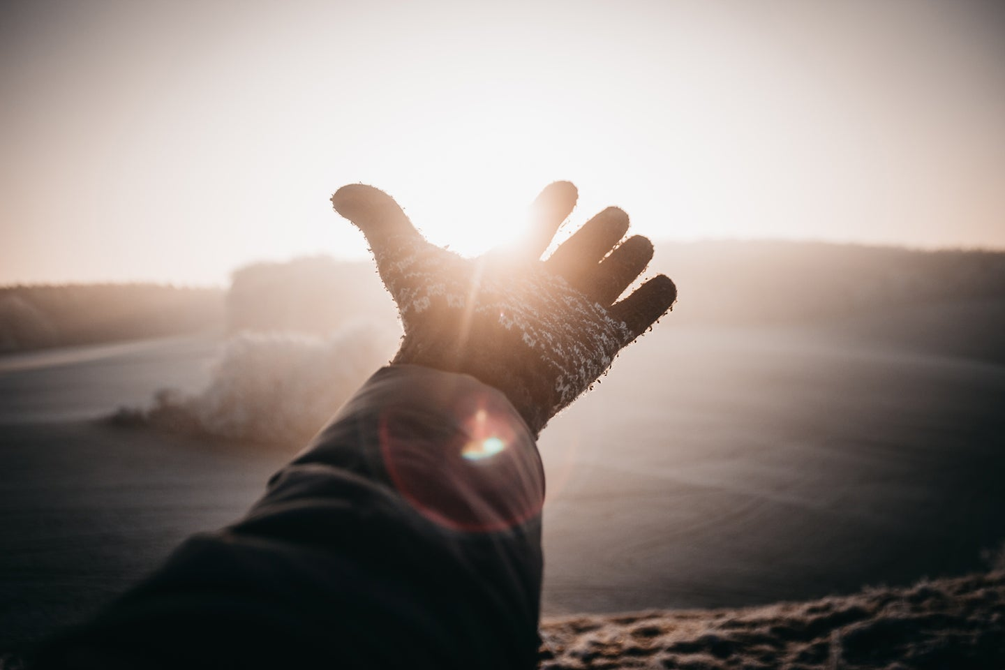 person with a glove reaching into the sky with the sun behind it