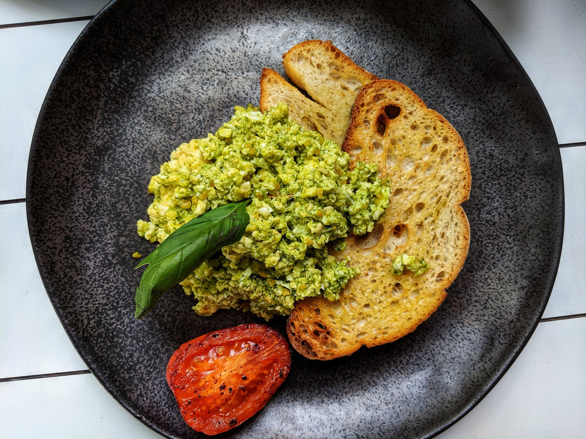 toast on a black plate with a tomato and guacamole