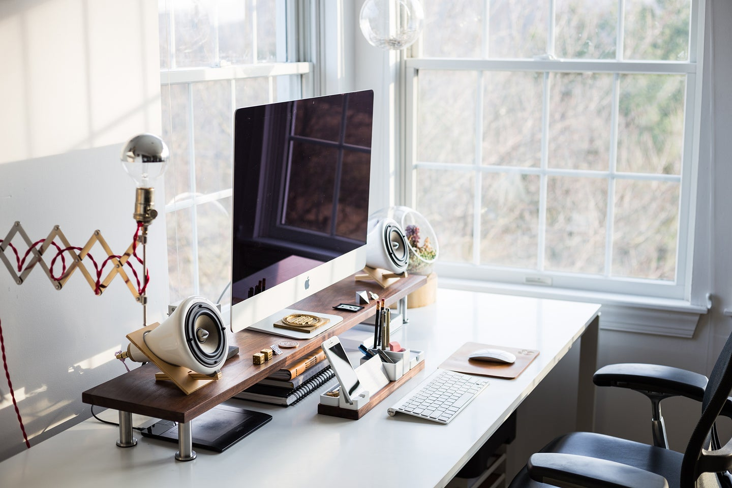 black desk chair in front of a desk with a computer, speakers, keyboard, phone, and mouse