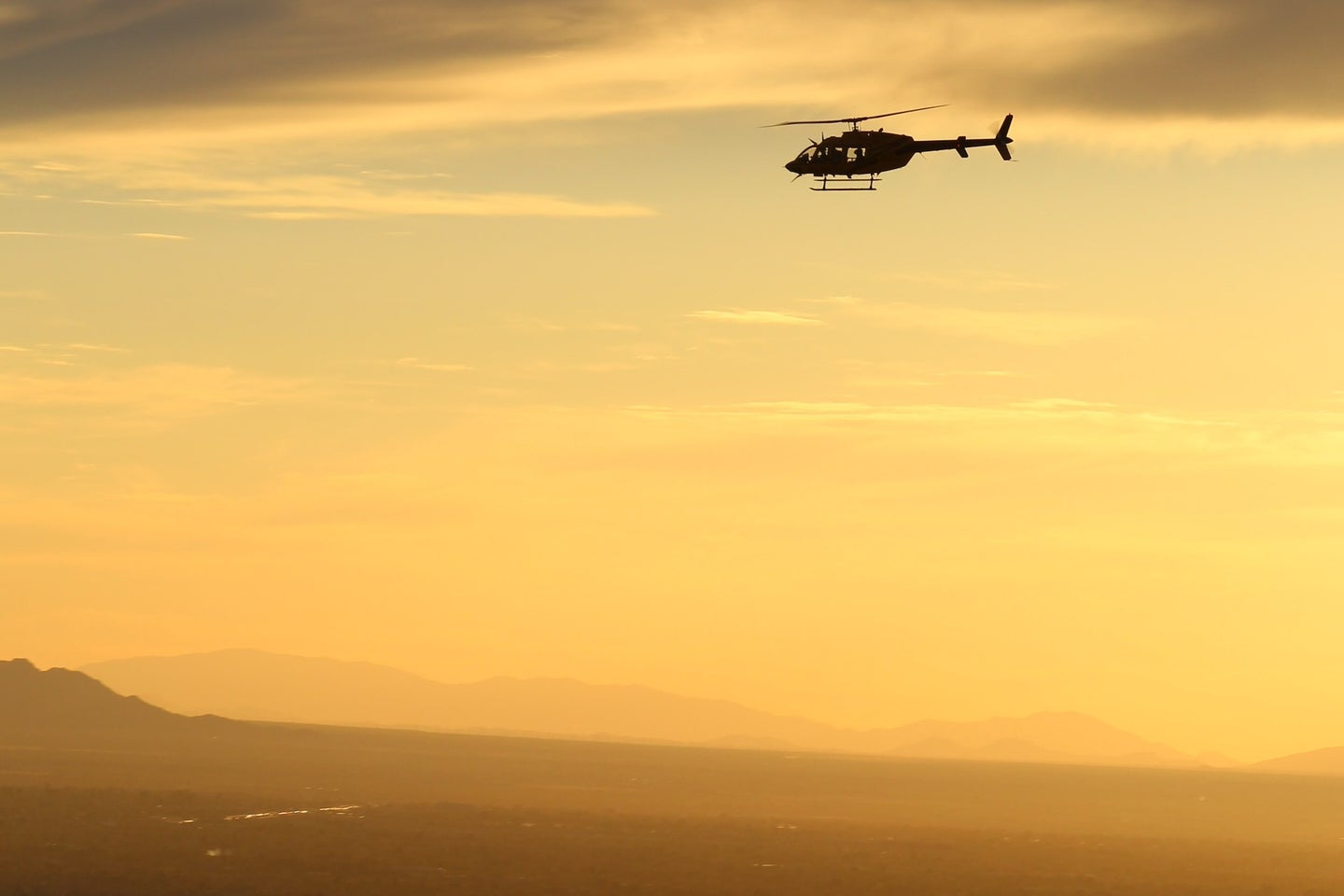 A helicopter flying at sunset.