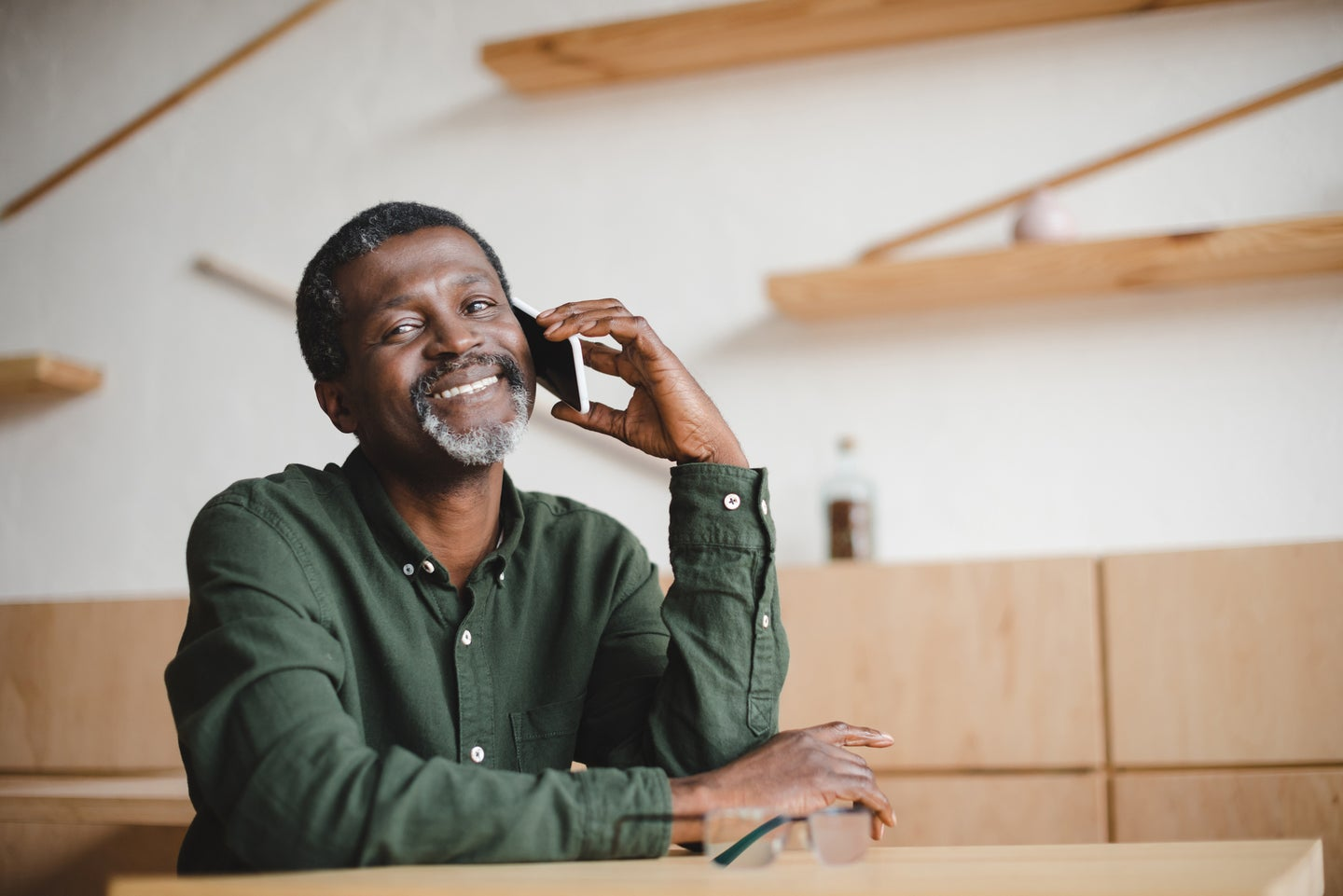 A Black middle-aged individual talking on a smartphone in a cafe