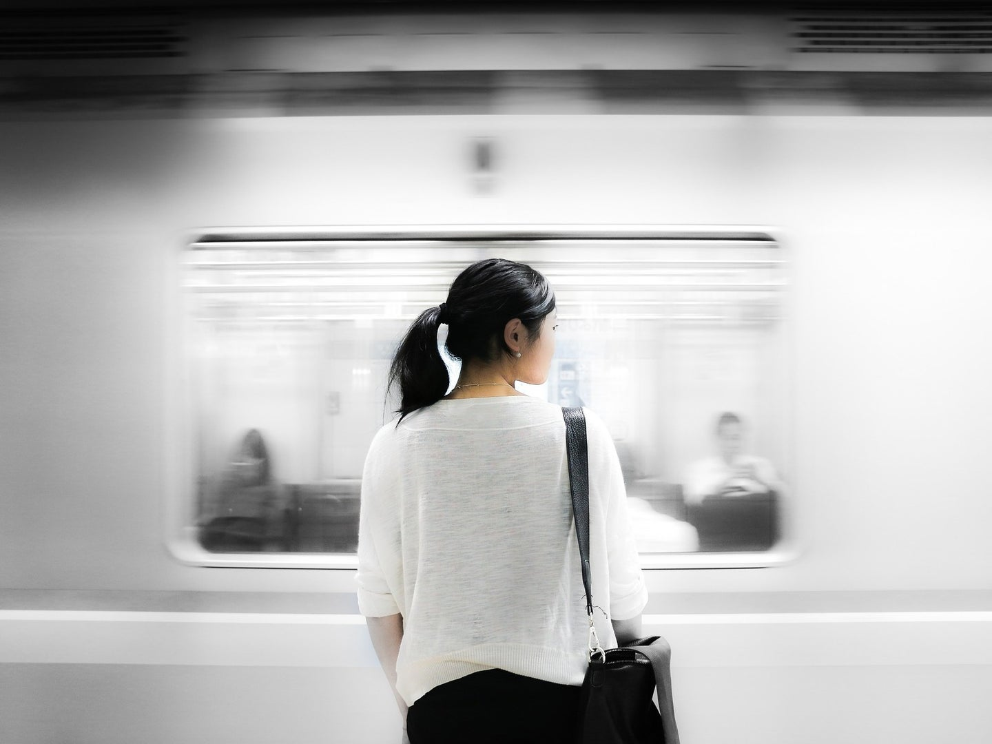 a woman getting ready to get on a mass transit subway