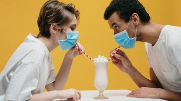 Couple drinking milkshakes with COVID-19 face masks on.
