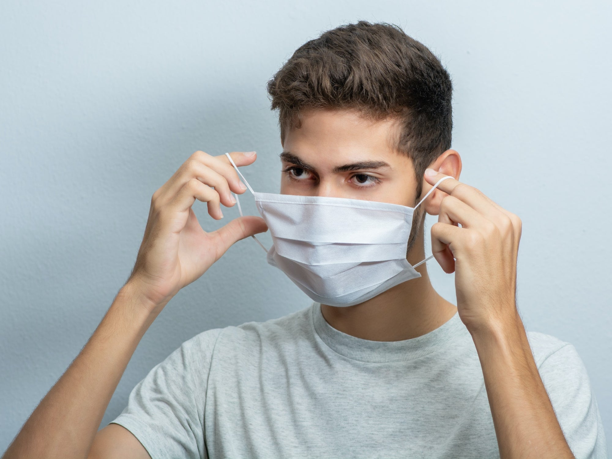 A man in a gray t-shirt removing or putting on a surgical face mask by only touching the ear loops.