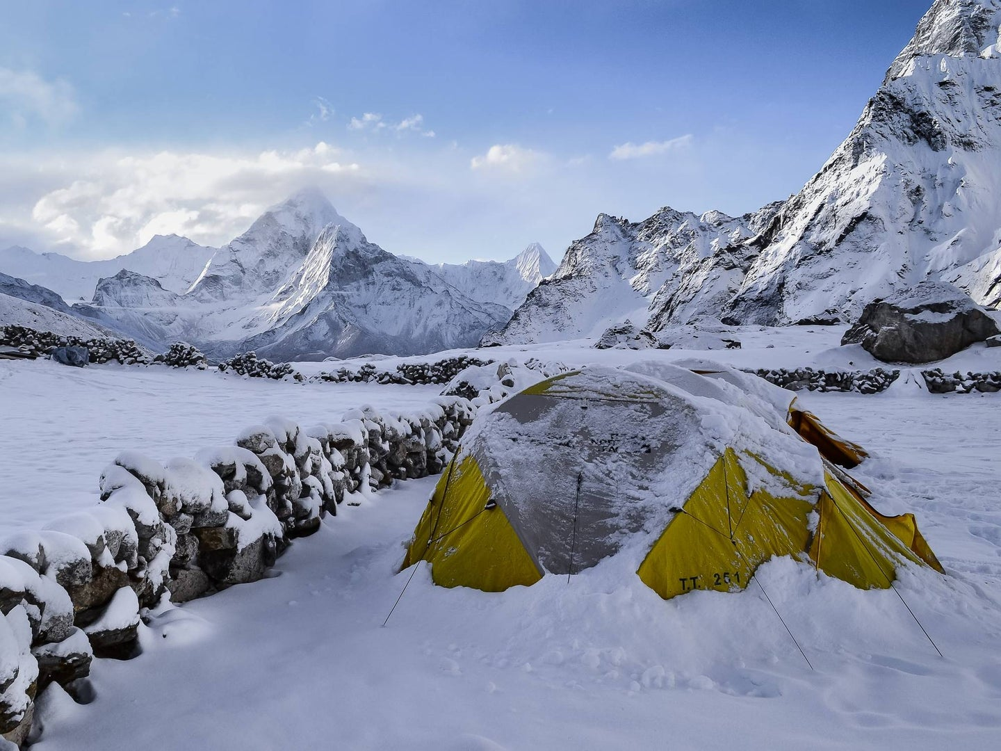 Green camping tent in the middle of a snowy mountain