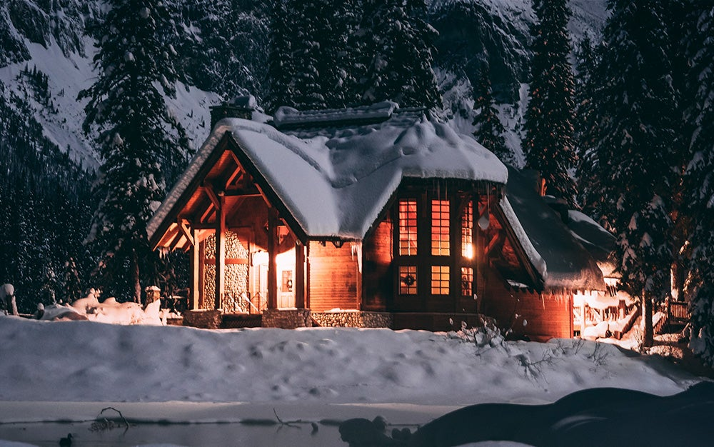 house with lights on covered in snow on a mountain