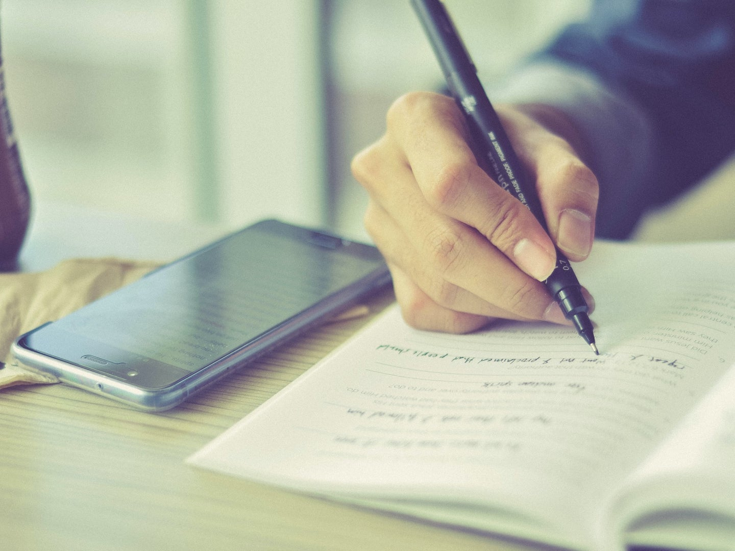 A person using a pen to write in a paper notebook, with a phone on the table next to them for storing digital notes.