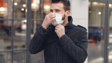 Bearded man wearing a surgical mask on the street