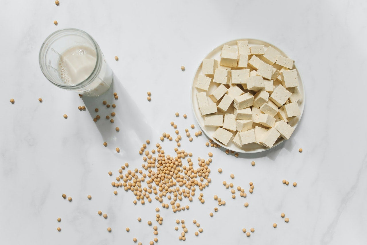 a bowl of tofu and a glass of soy milk on a white marble counter, with dried soybeans scattered around the surface