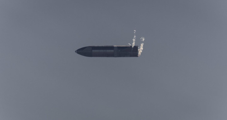 A SpaceX Starship rocket falls through the air horizontally during a test.