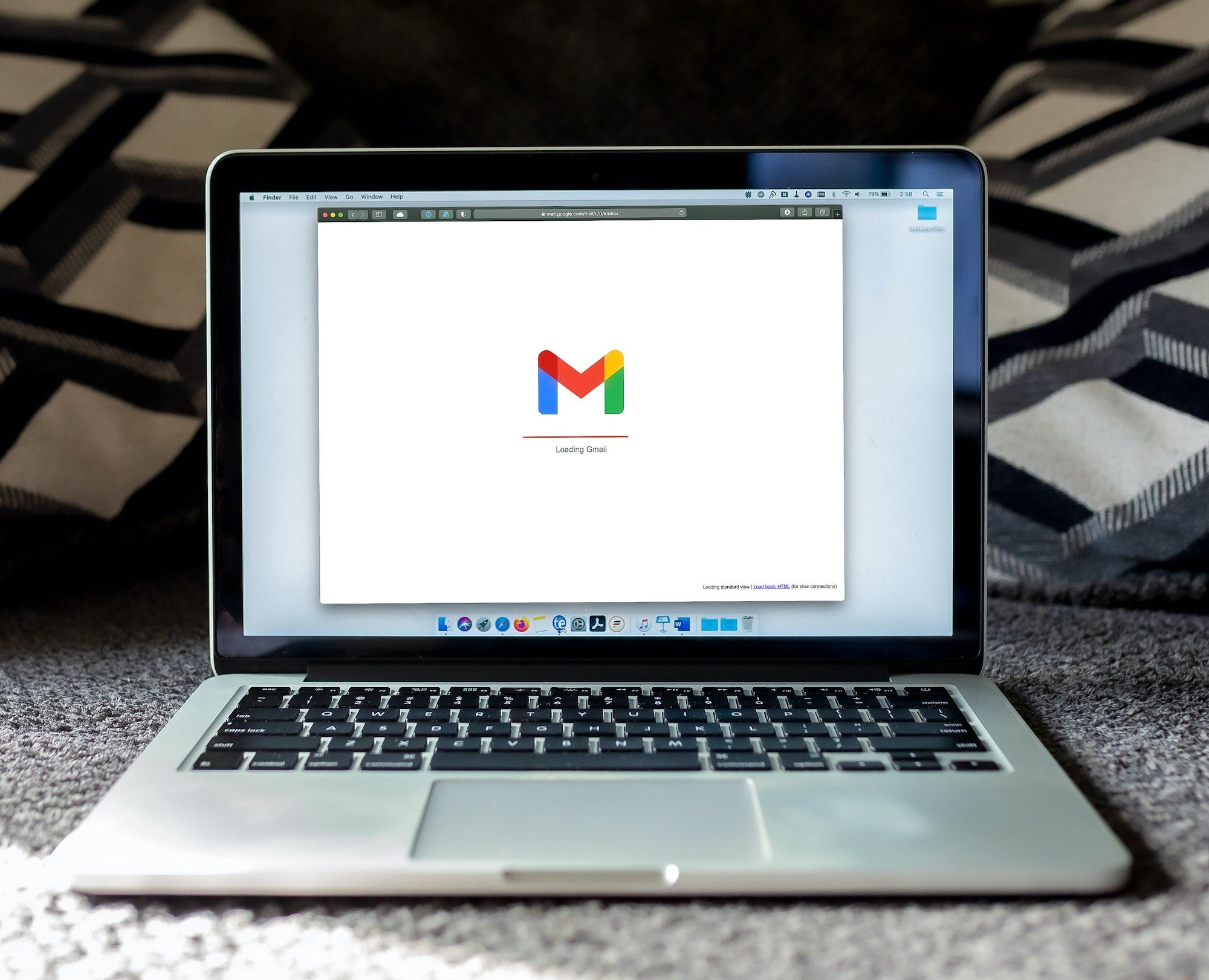 A MacBook displays a loading Gmail icon.