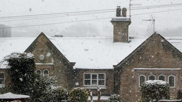 A stone building under power lines during a snowstorm.