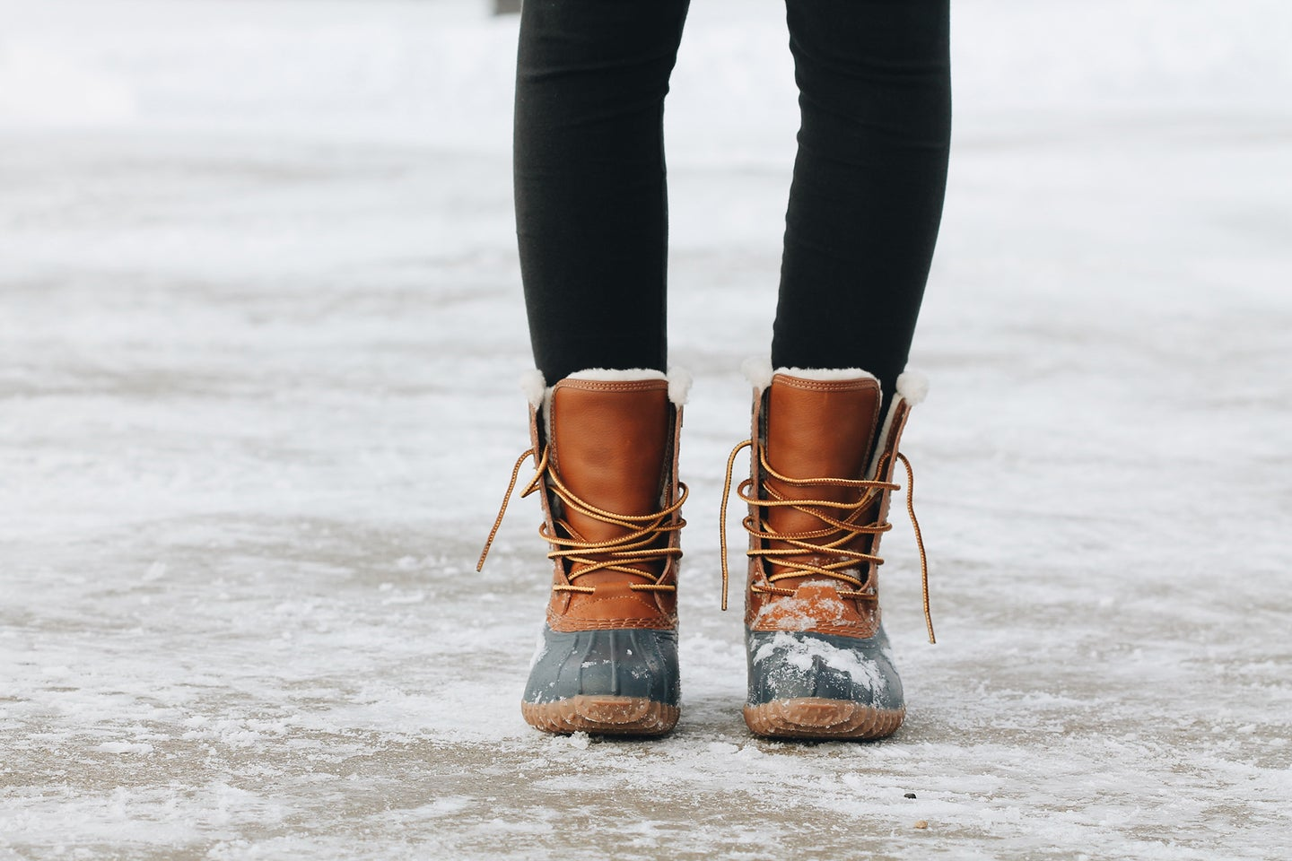 person in brown winter boots standing on a snowy and icy ground