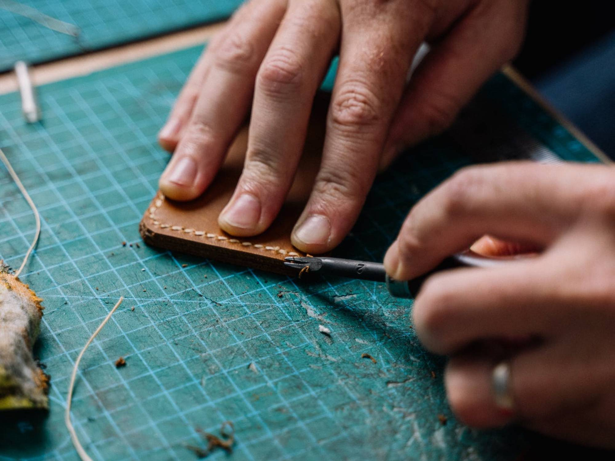 Hands working on edging a piece of leatherwork