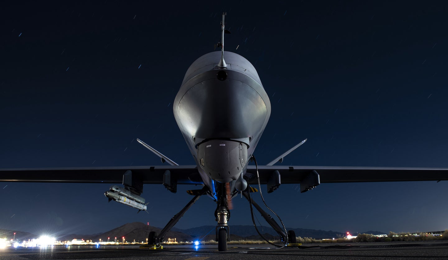 A Reaper drone on the ground armed with a missile.