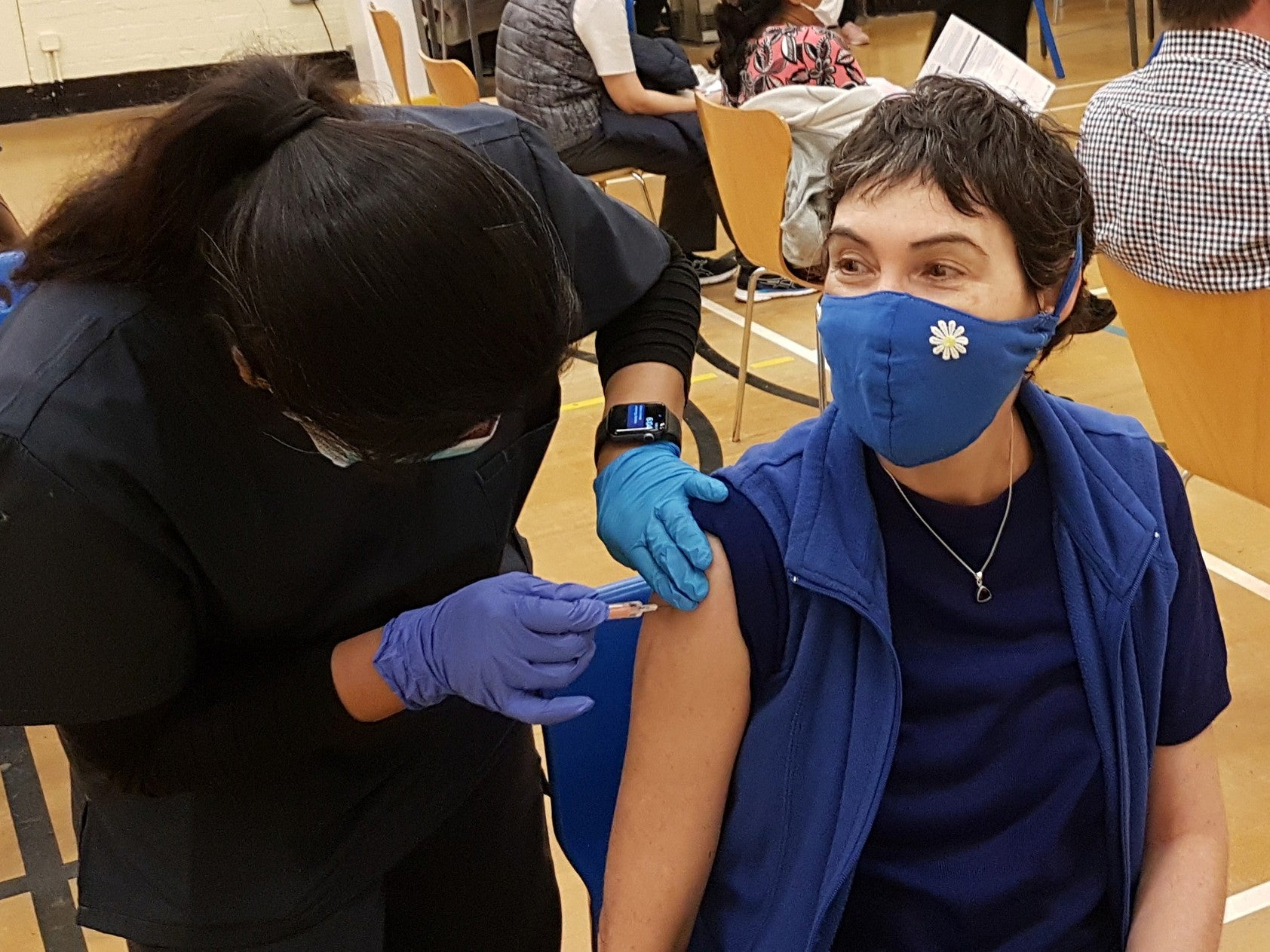 someone getting a COVID-19 vaccine with a mask on.