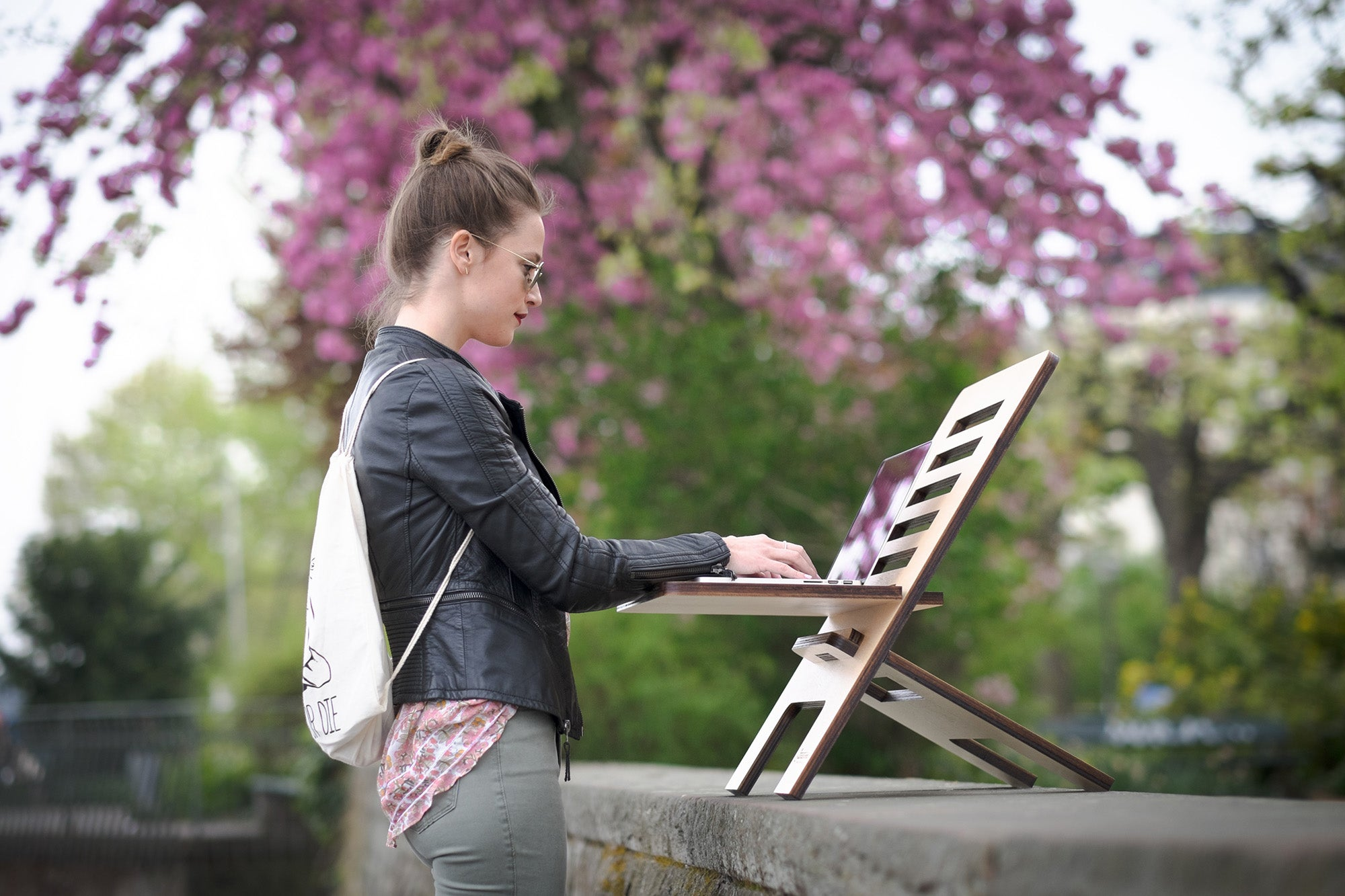 A woman outside, using the best portable wifi, with a white backpack working on a laptop placed on a folding laptop stand.