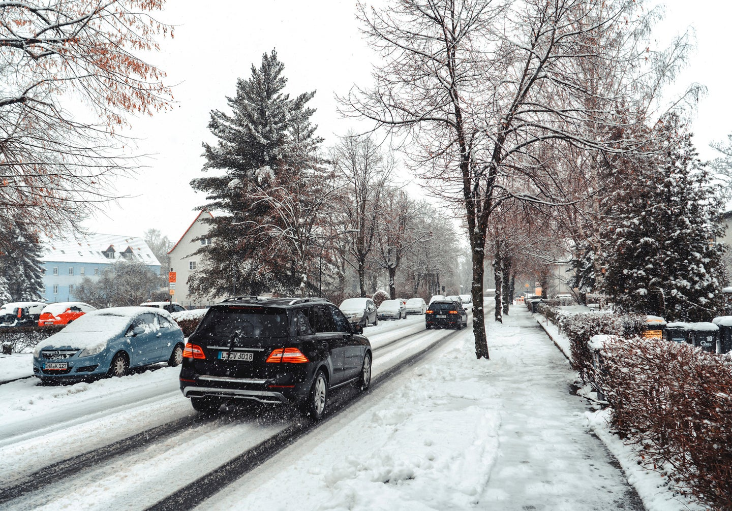snowy street with tress, parked cars, and cars driving