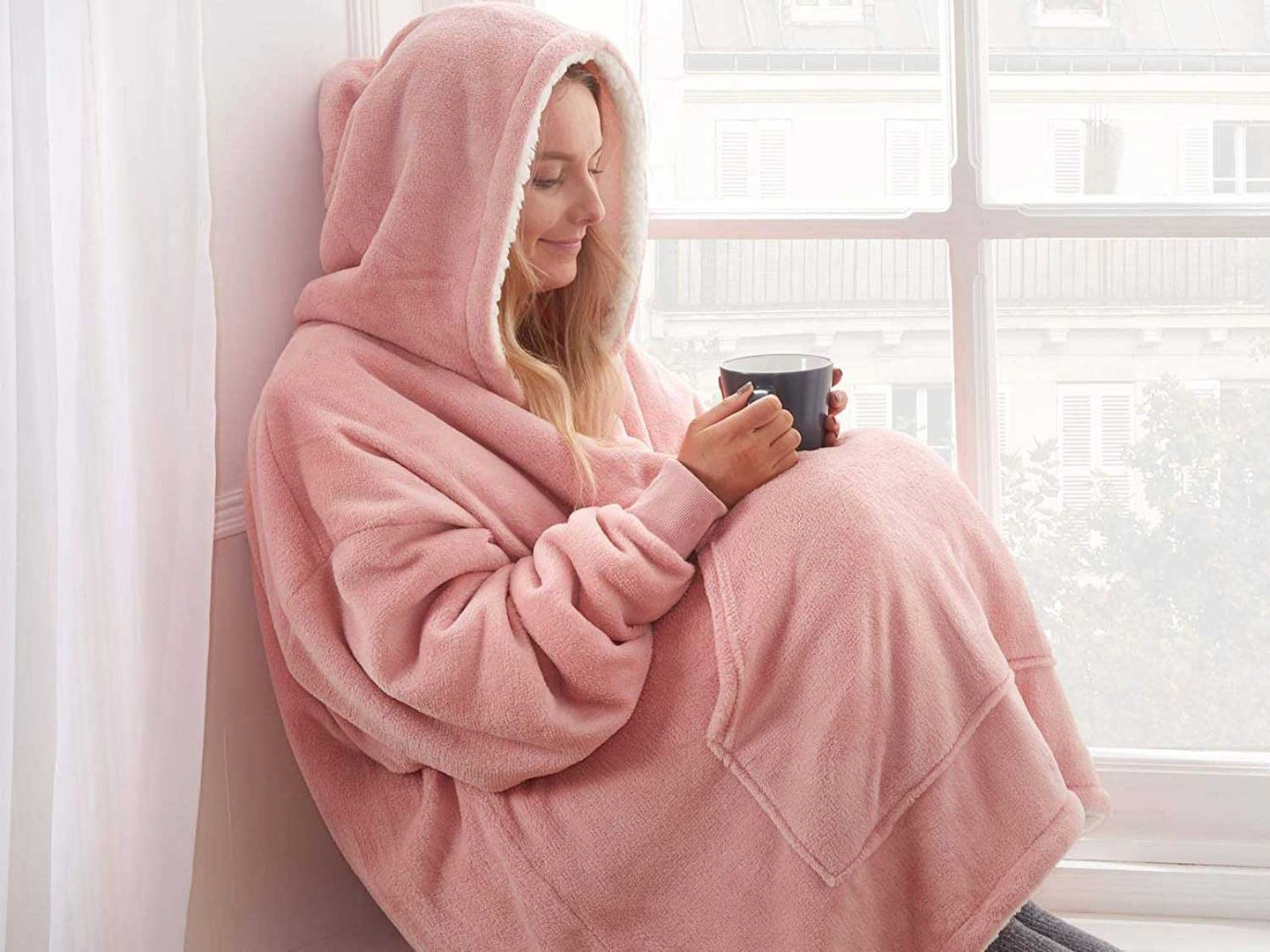 Woman holding cup of coffee wearing cozy and warm hoodie blanket.