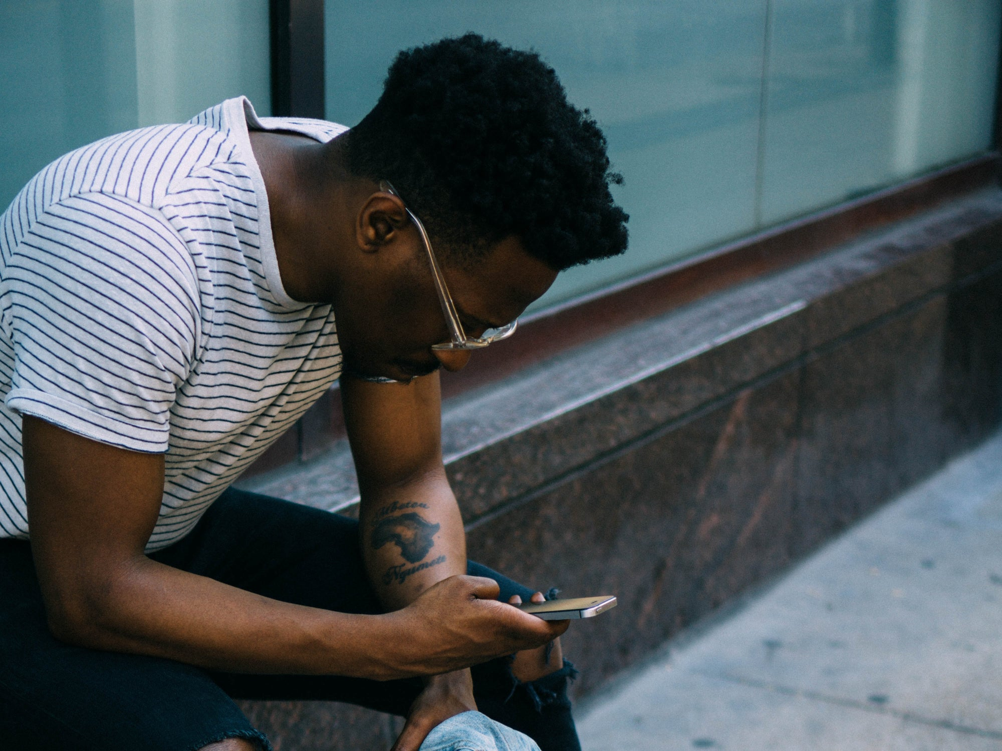 A Black man in glasses and a t-shirt sitting on a marble wall, looking at a phone.