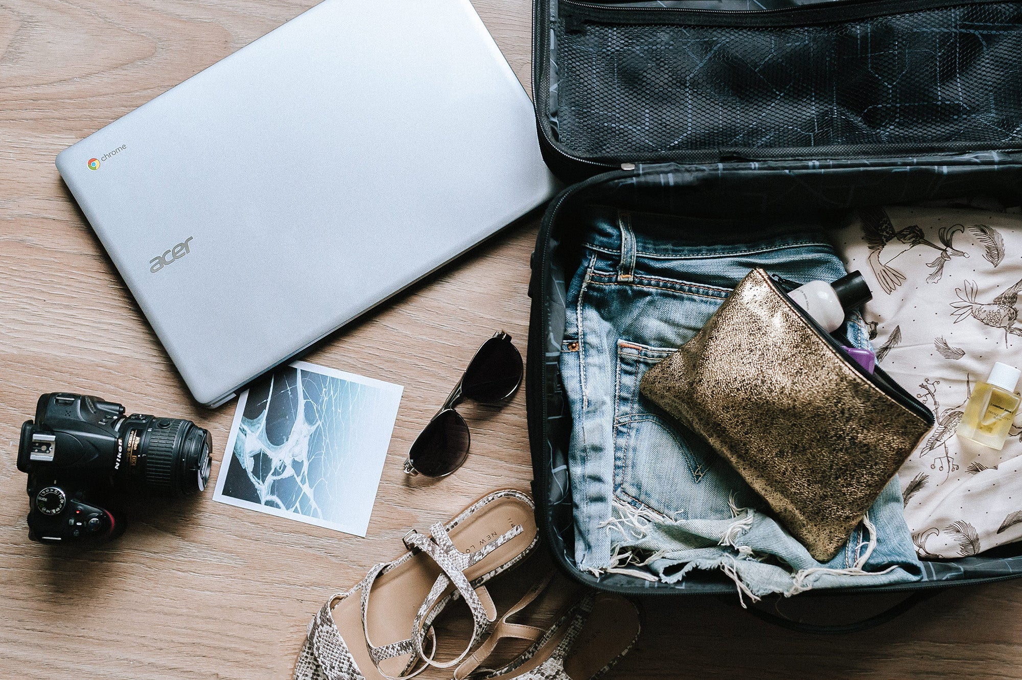 suitcase, laptop, sunglasses, camera, and other travel gear for the best gifts for travelers