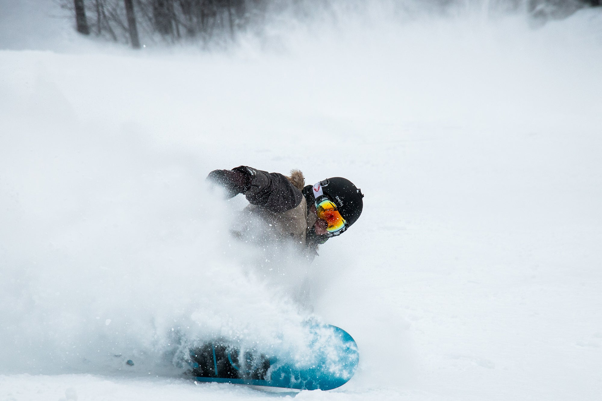 person snowboarding with helmet and the best snowboard goggles and carving through some snow
