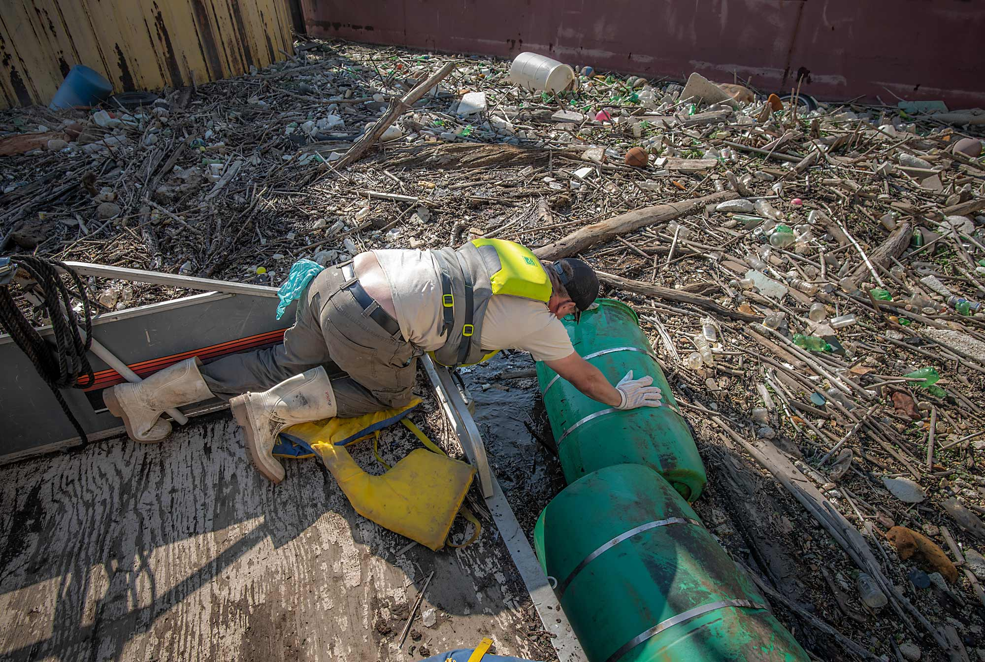 a boat captain tries to pull a plastic barrel from a debris island