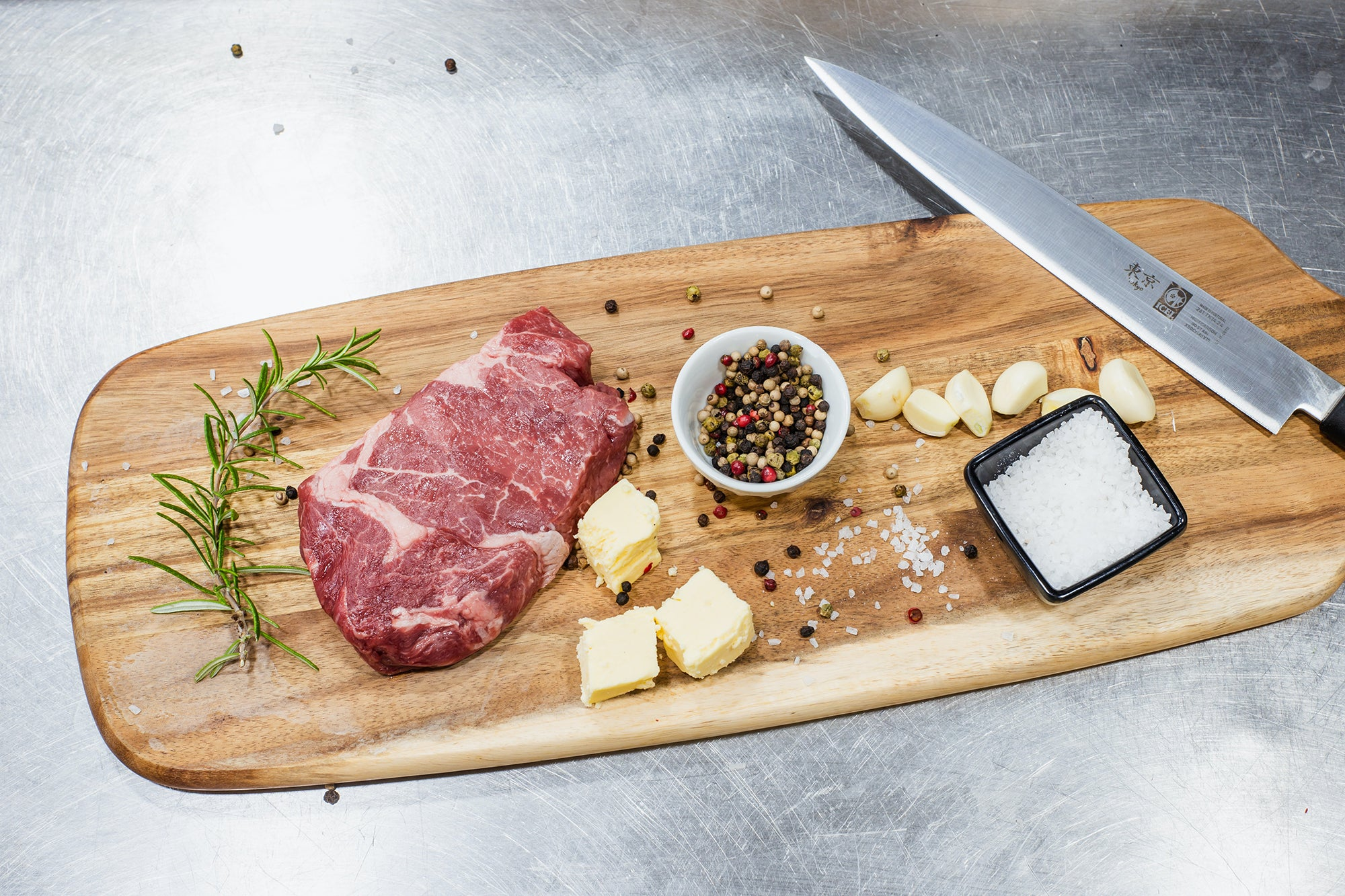 meat, cheese, pepper, and salt on a wood board next to a kitchen knife