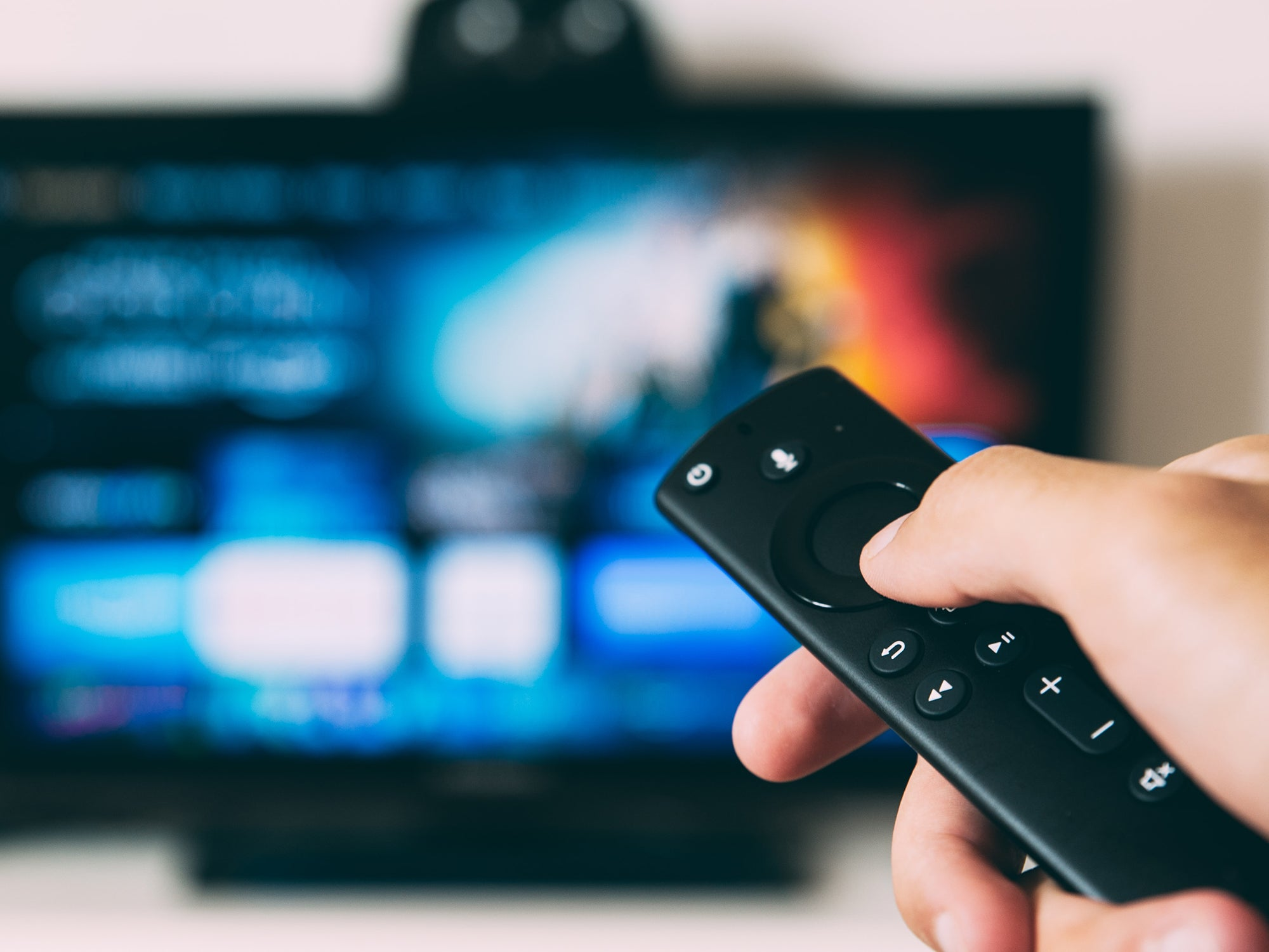 Hand holding Amazon Fire TV remote towards TV screen