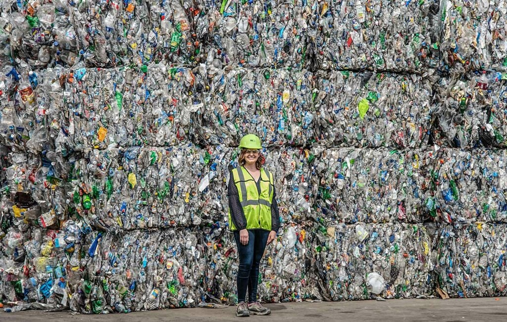 spokesperson for Waste Management stands with bales of plastic garbage