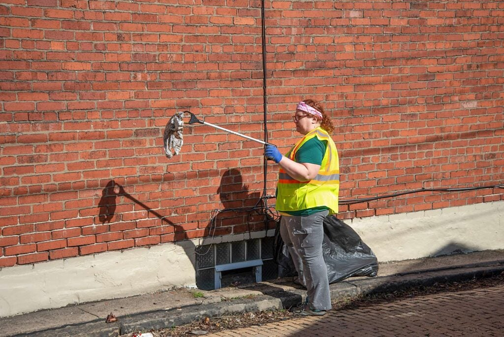 A volunteer in a clean-up crew picks up a piece of discarded plastic