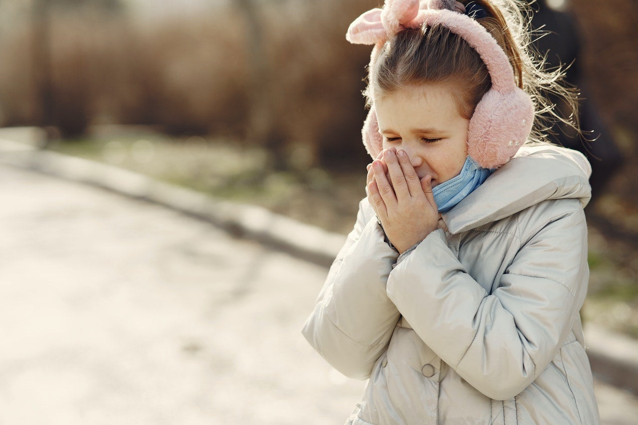 A young girl stands outside in a winter coat, pink earmuffs, and a blue face mask pulled down over her chin as she sneezes into her hands.