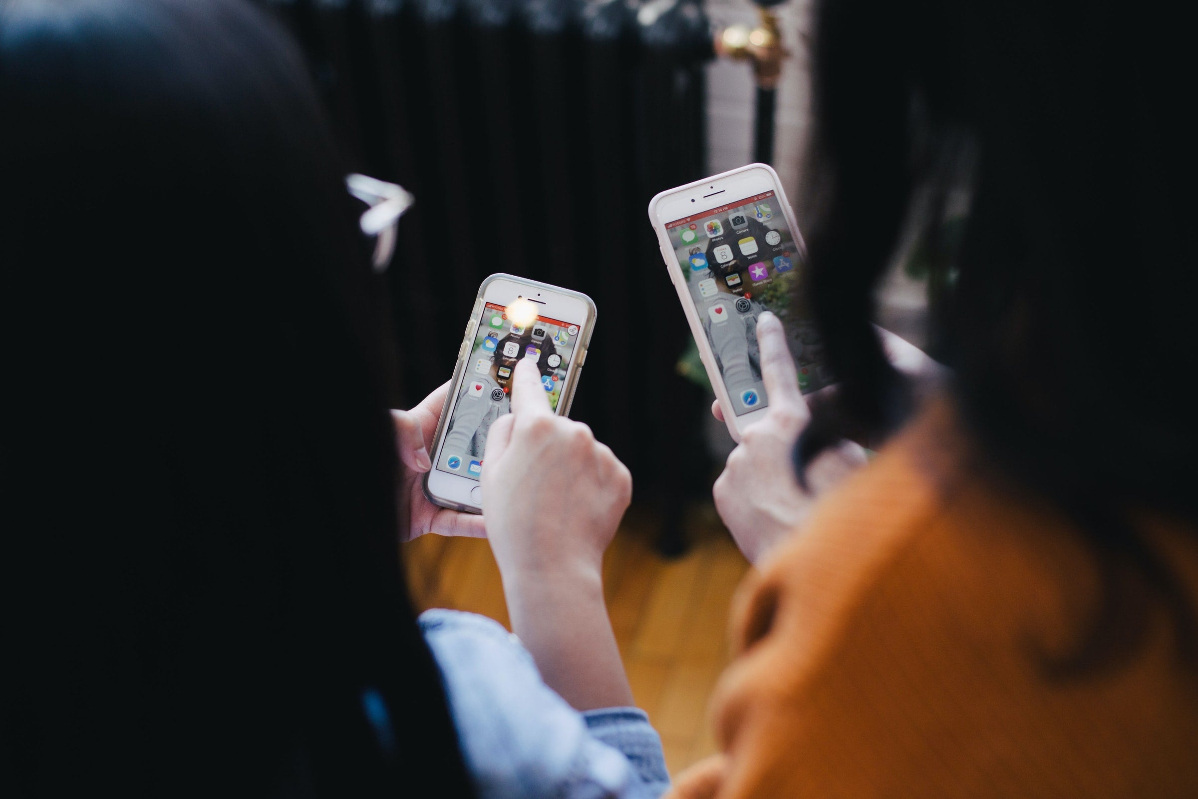 Two people facing away from the camera while pointing at their iPhones.