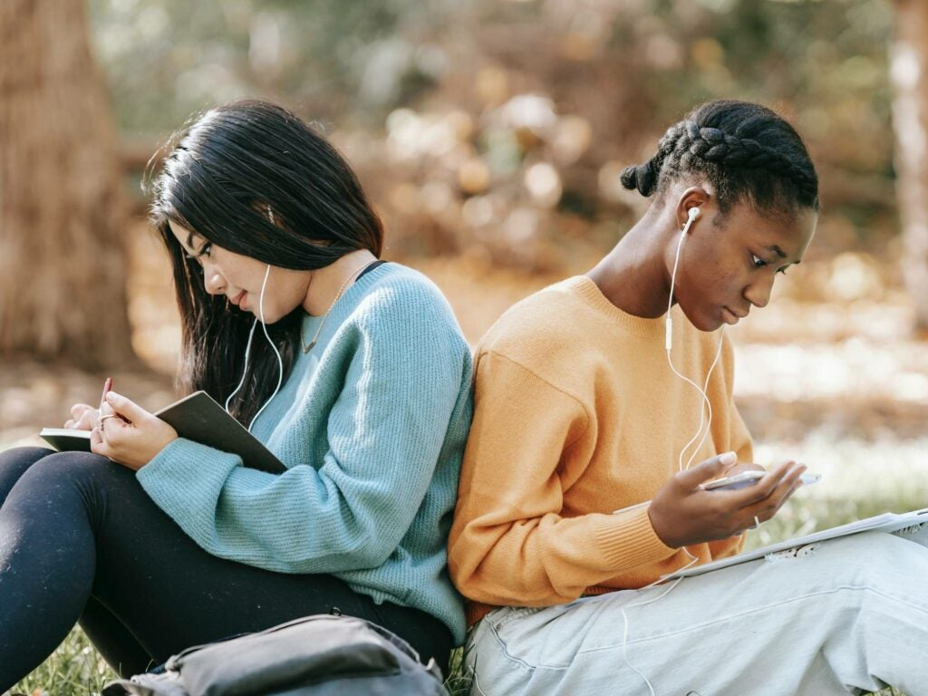 Young people back to back, sitting in a park, studying with their phones.