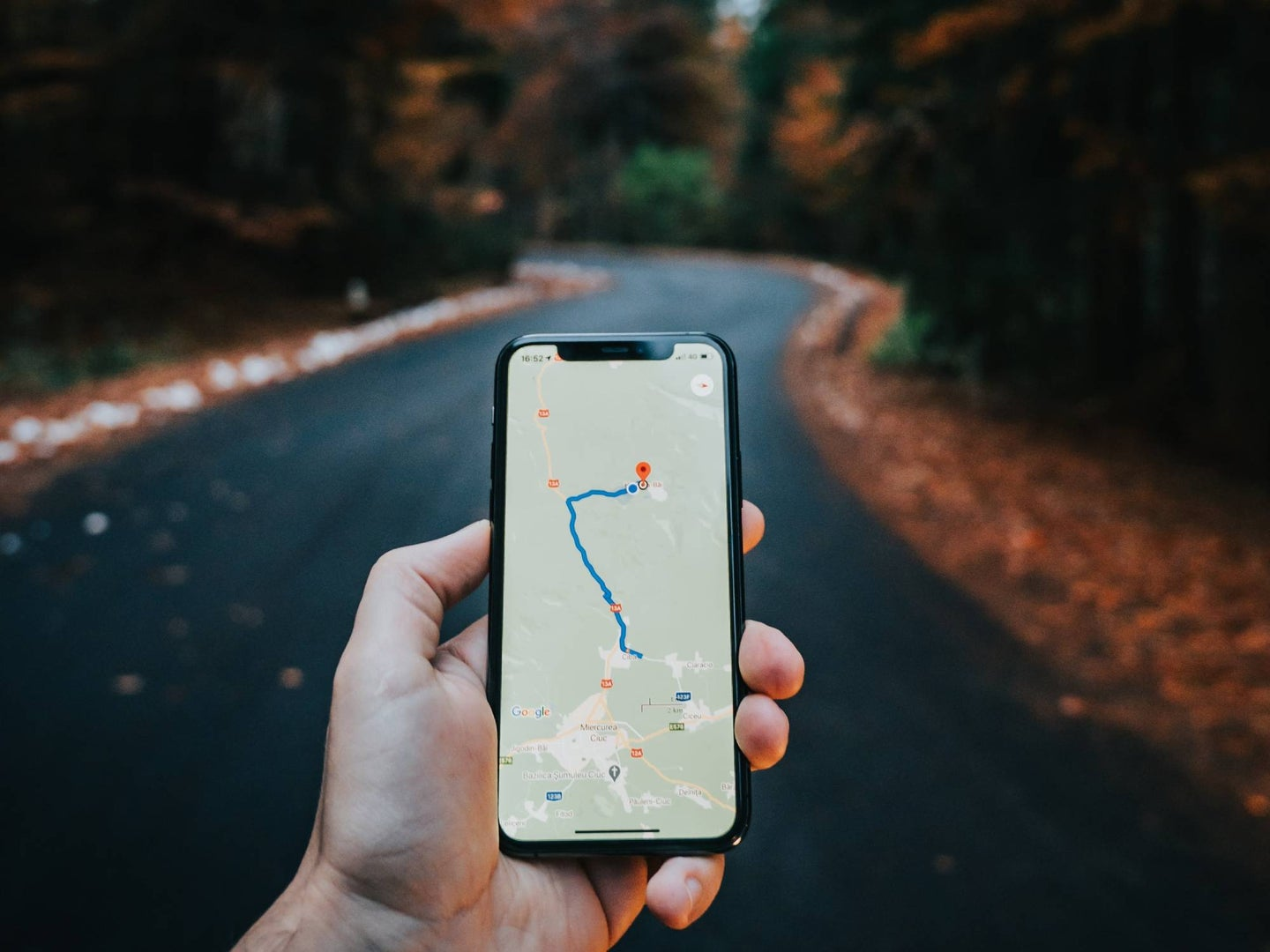 Hand holding a phone with a map in front of an empty road.