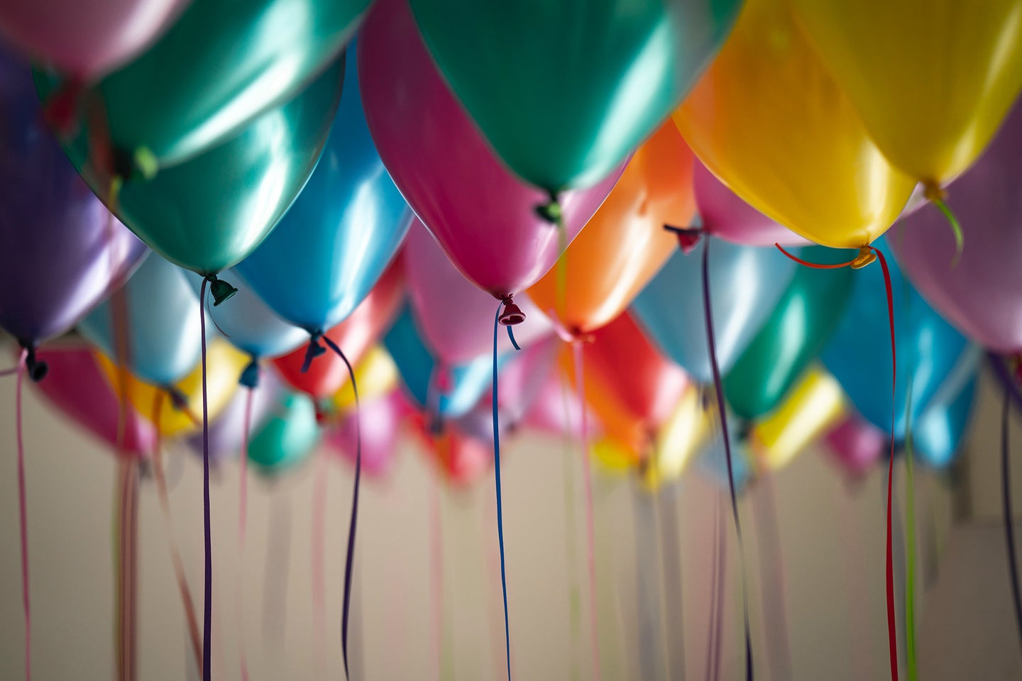 multiple colors of balloons with string hanging