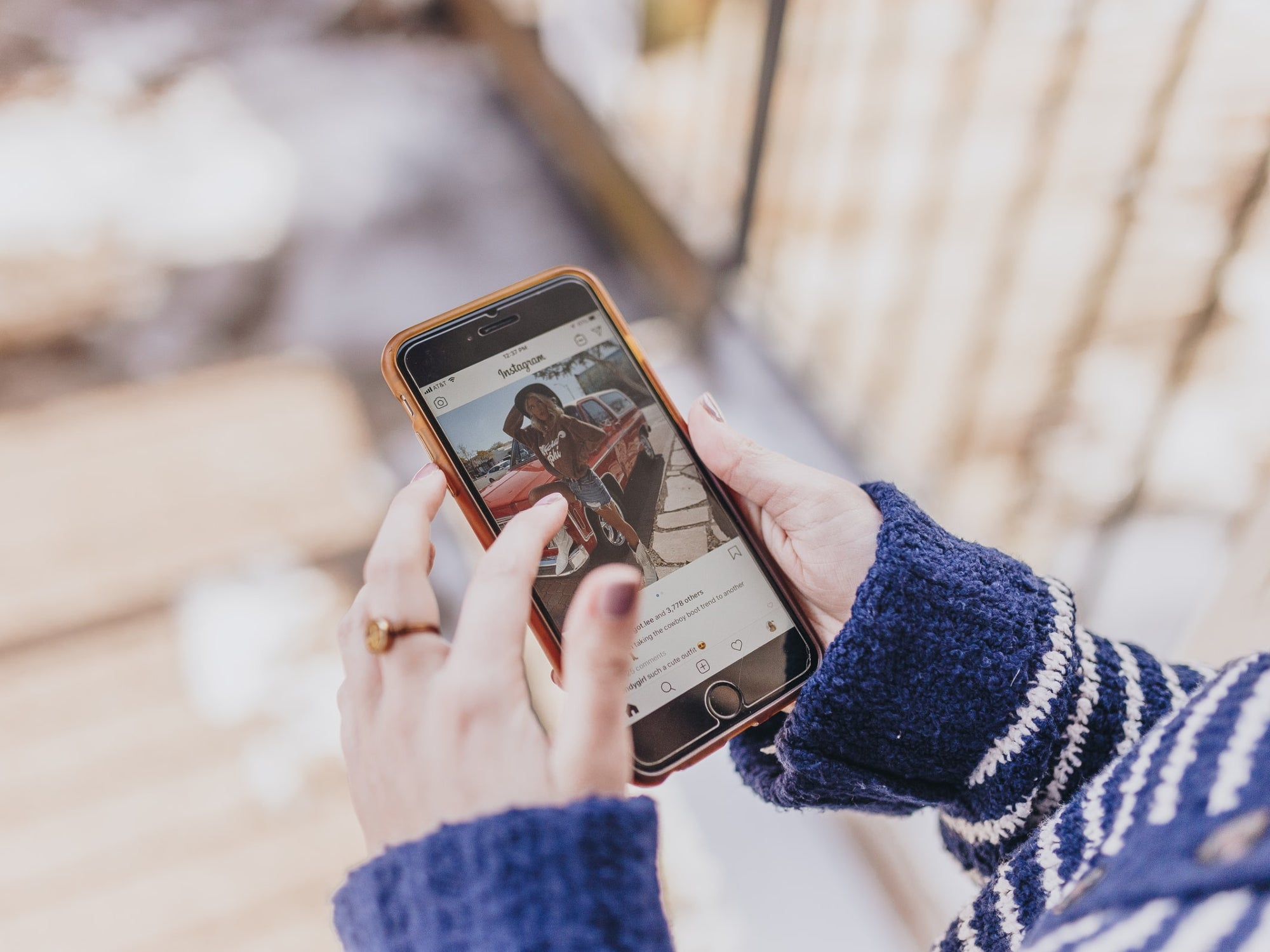 A person holding their phone and looking at a photo on Instagram.