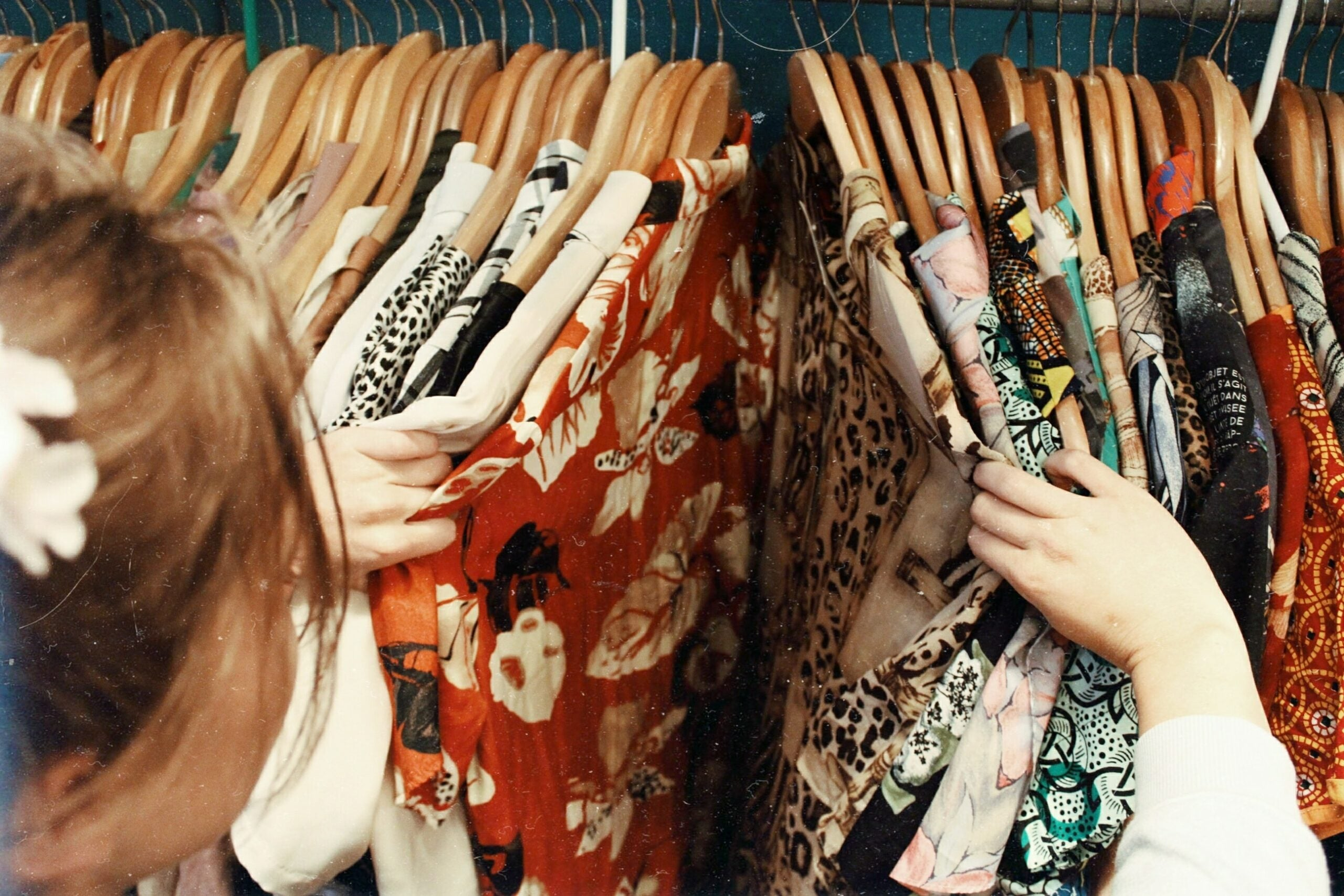 Woman searching through rack of vintage second-hand thrift clothing.
